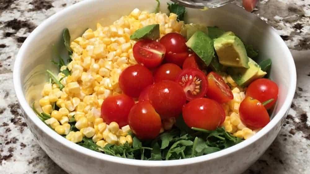 adding tomatoes and avocado to fresh corn salad