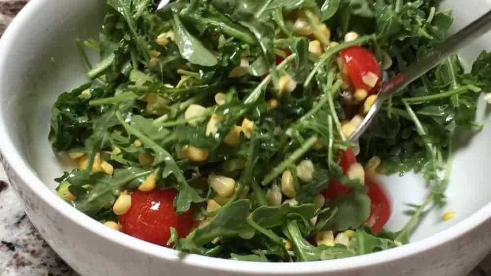 tossing fresh corn salad