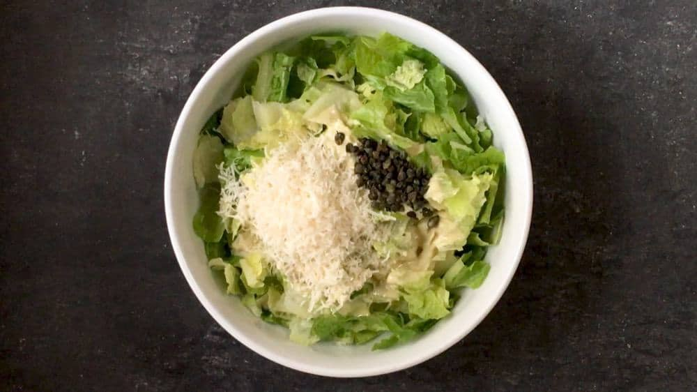 Caesar Salad ingredients in a white bowl ready to toss
