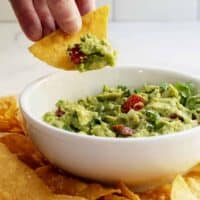 dipping guacamole with a tortilla chip