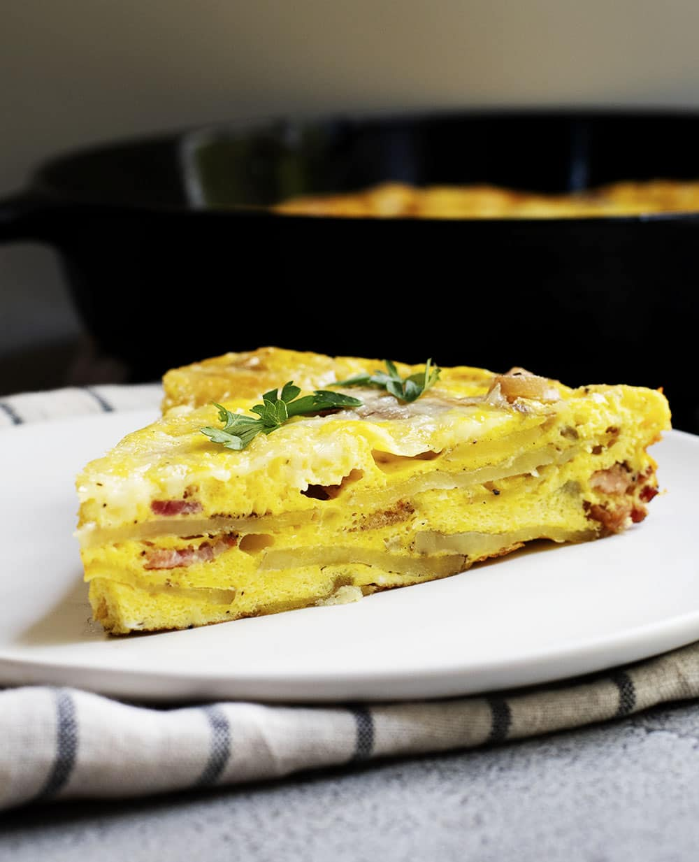 wedge of breakfast frittata served on a white plate