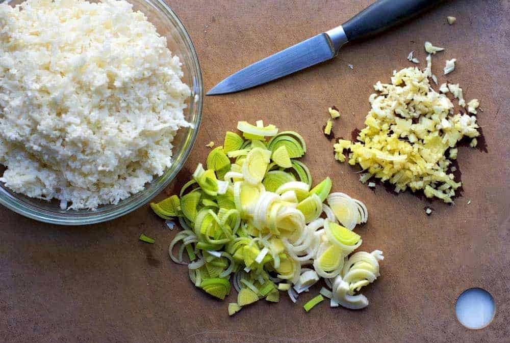 Cauliflower Rice Leeks Garlic and Ginger with a paring knife on a cutting board