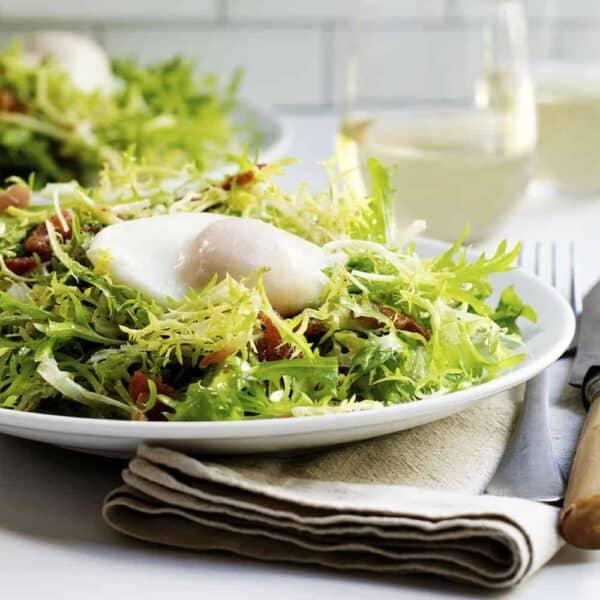 Salad Lyonnaise served on a white plate