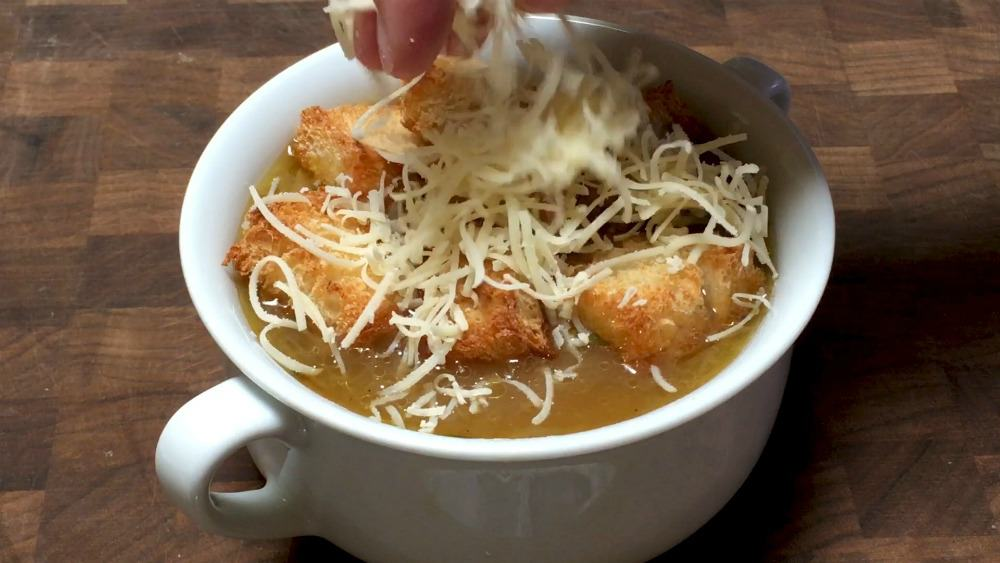 topping french onion soup with croutons and gruyere cheese