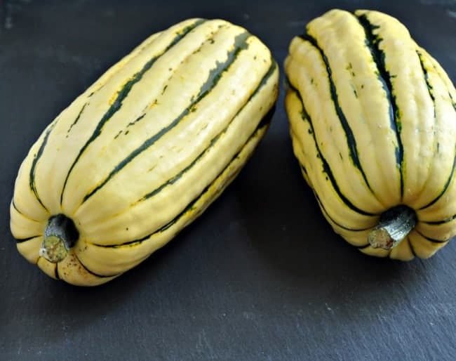Two uncooked delicata squash on counter