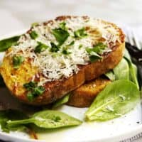 savory french toast served with mixed baby greens on a white plate