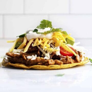 Pork Carnitas Tostada on a marble slab