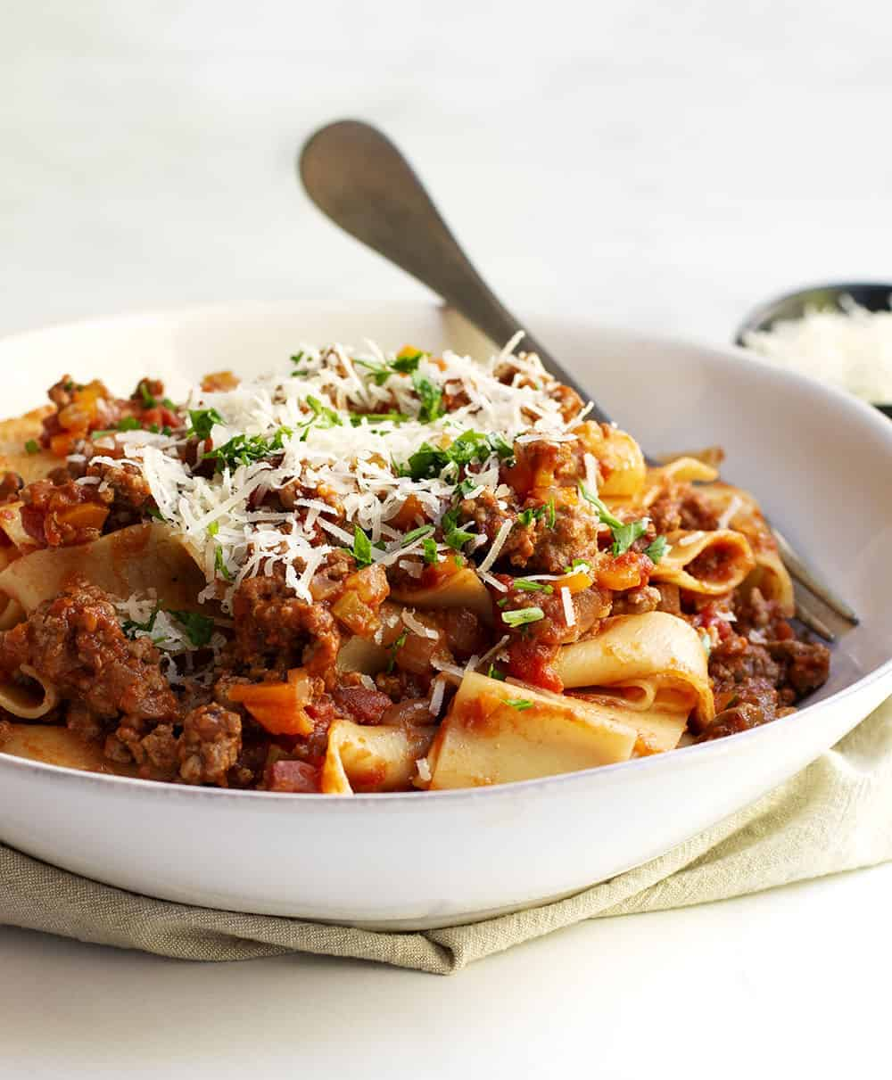 Bolognese Sauce with pappardelle served in a shallow white bowl