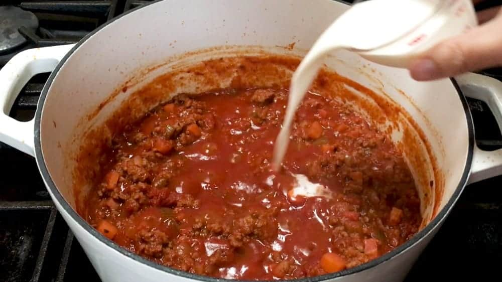 adding cream to bolognese sauce