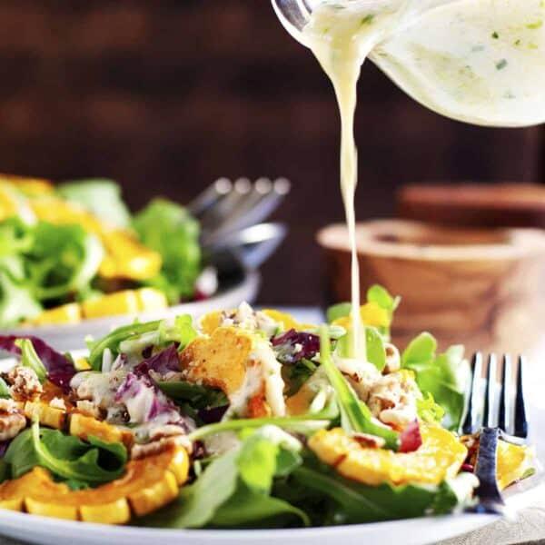 pouring dressing over Delicata Squash Salad