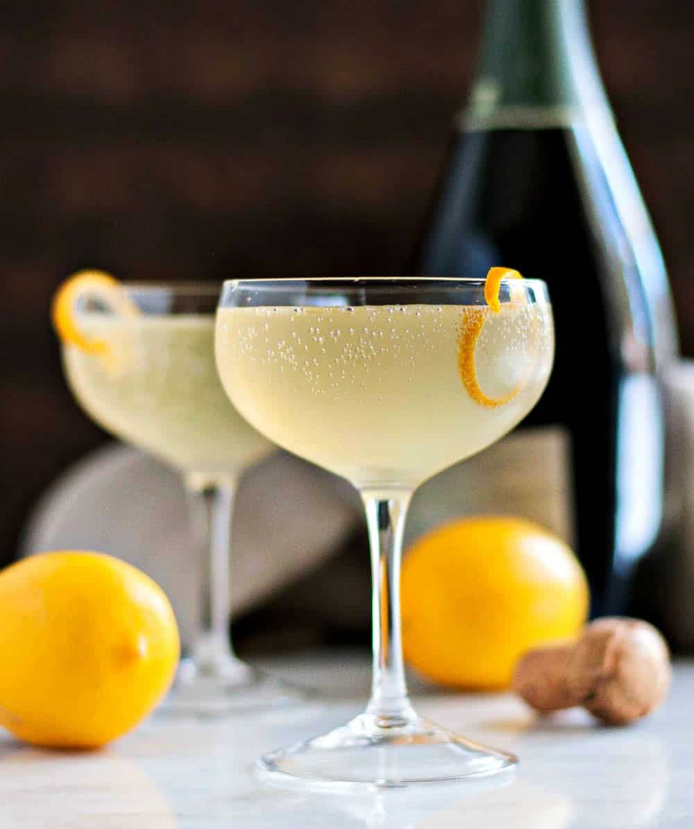 French 75 cocktails with lemons and Champagne in the background