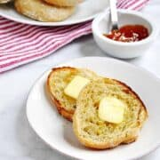 Homemade-English-Muffins-topped-with-Melting-Butter served on white plates featured