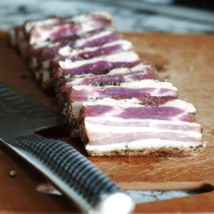 Homemade Pancetta sliced on a cutting board