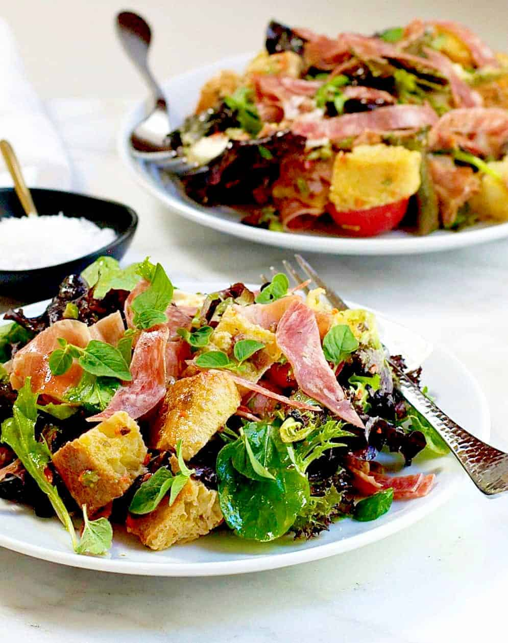 Muffuletta Panzanella Bread Salad served on white plates