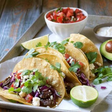 Three Carne Asada tacos on a plate with lime and avocado.