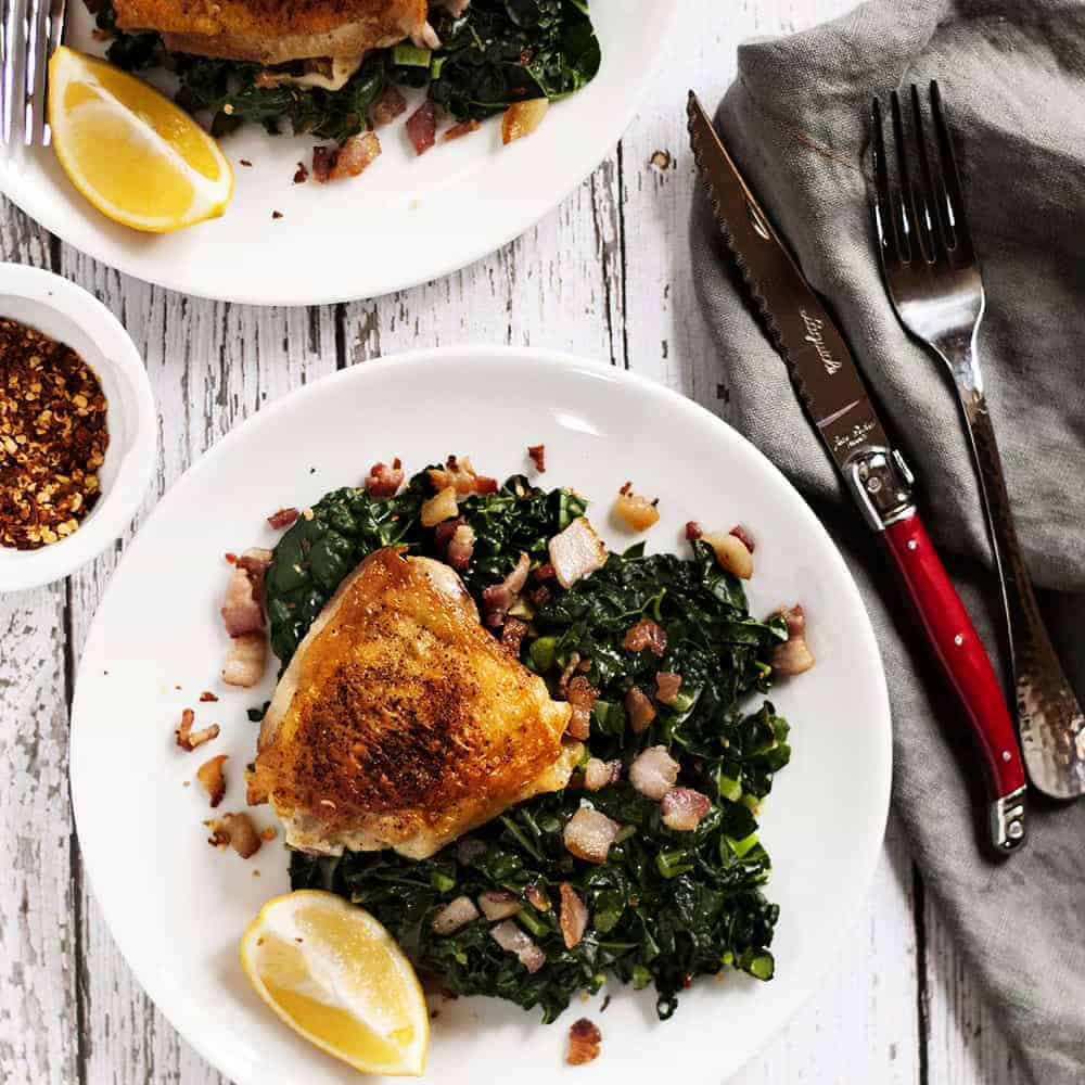 Crispy-Chicken-Thighs-with-Kale-and-Bacon on white plates
