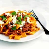 Lamb-Ragu-with-Pappardelle served on a white plate with fork