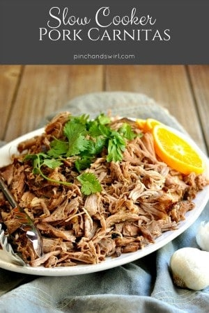 Pork carnitas served on a white platter with an orange slice.
