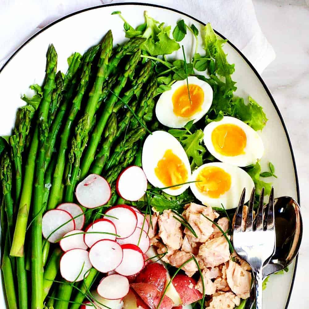 Asparagus-Nicoise-Salad on a white platter featured