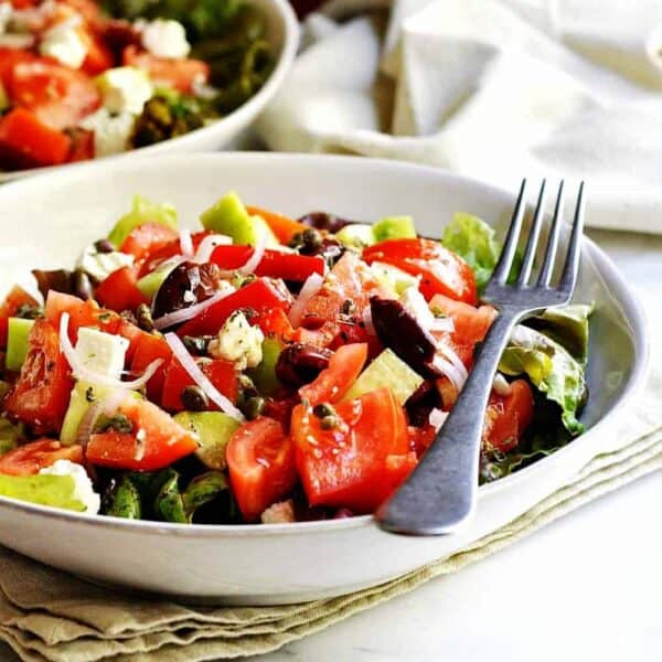 Greek-Salad served in white bowls featured