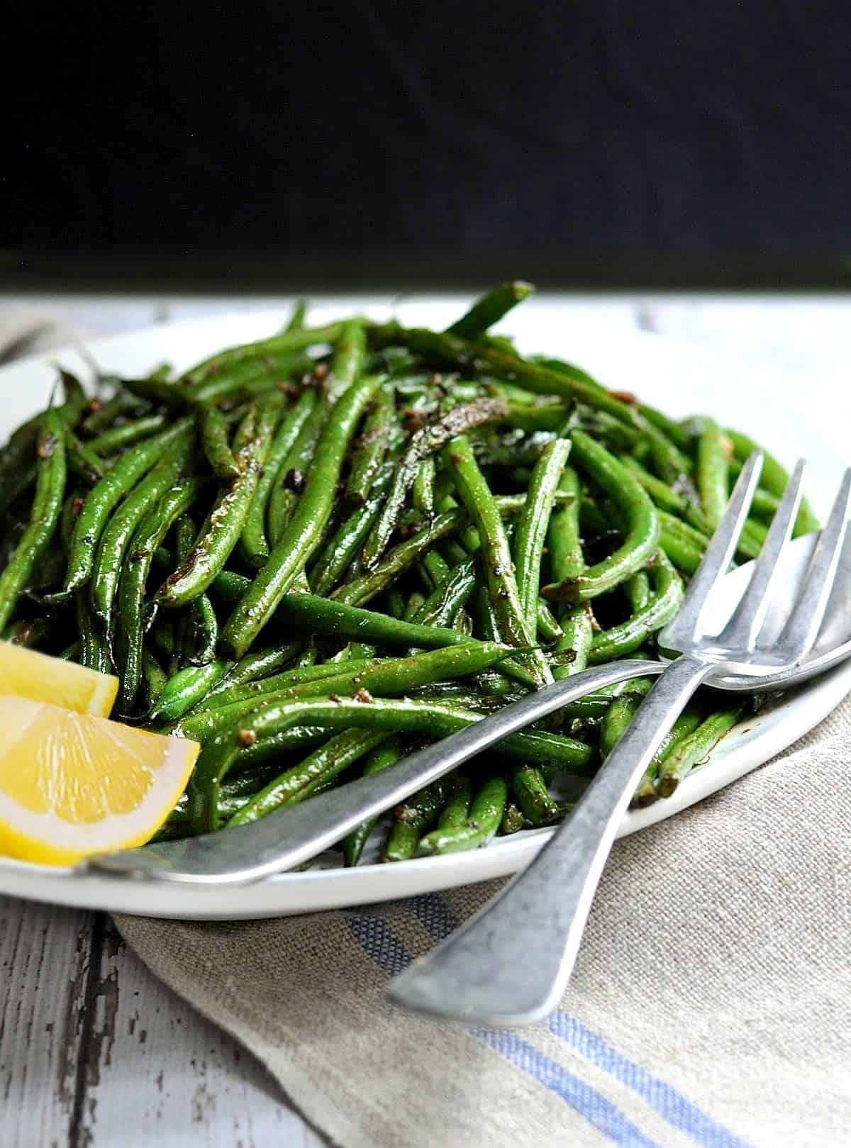 Grilled Green Beans and Lemon Wedge on a white platter