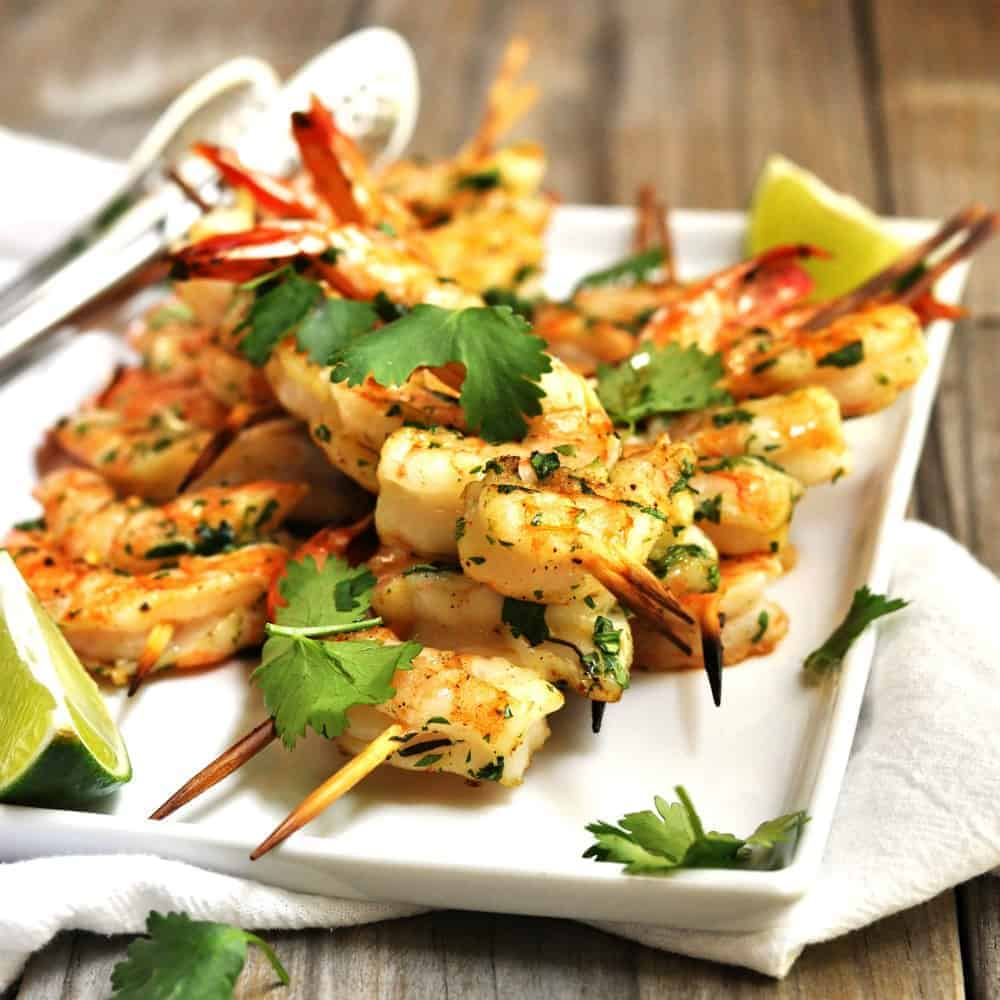 Grilled Shrimp skewers served on a white platter square