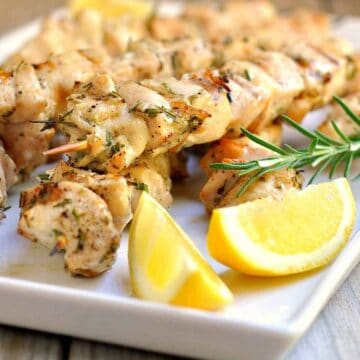 Rosemary garlic chicken kabobs on a white serving tray with fresh lemon.