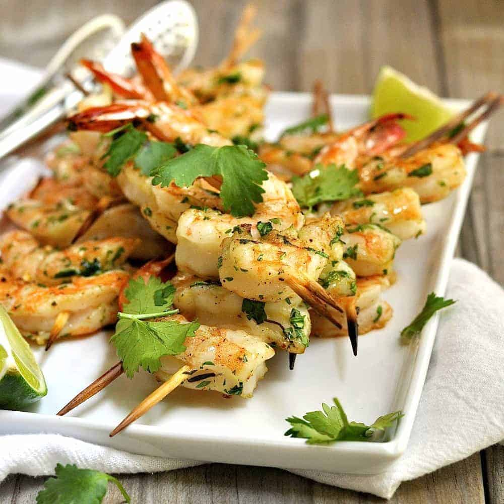 Spice grilled shrimp skewers on a white serving tray.
