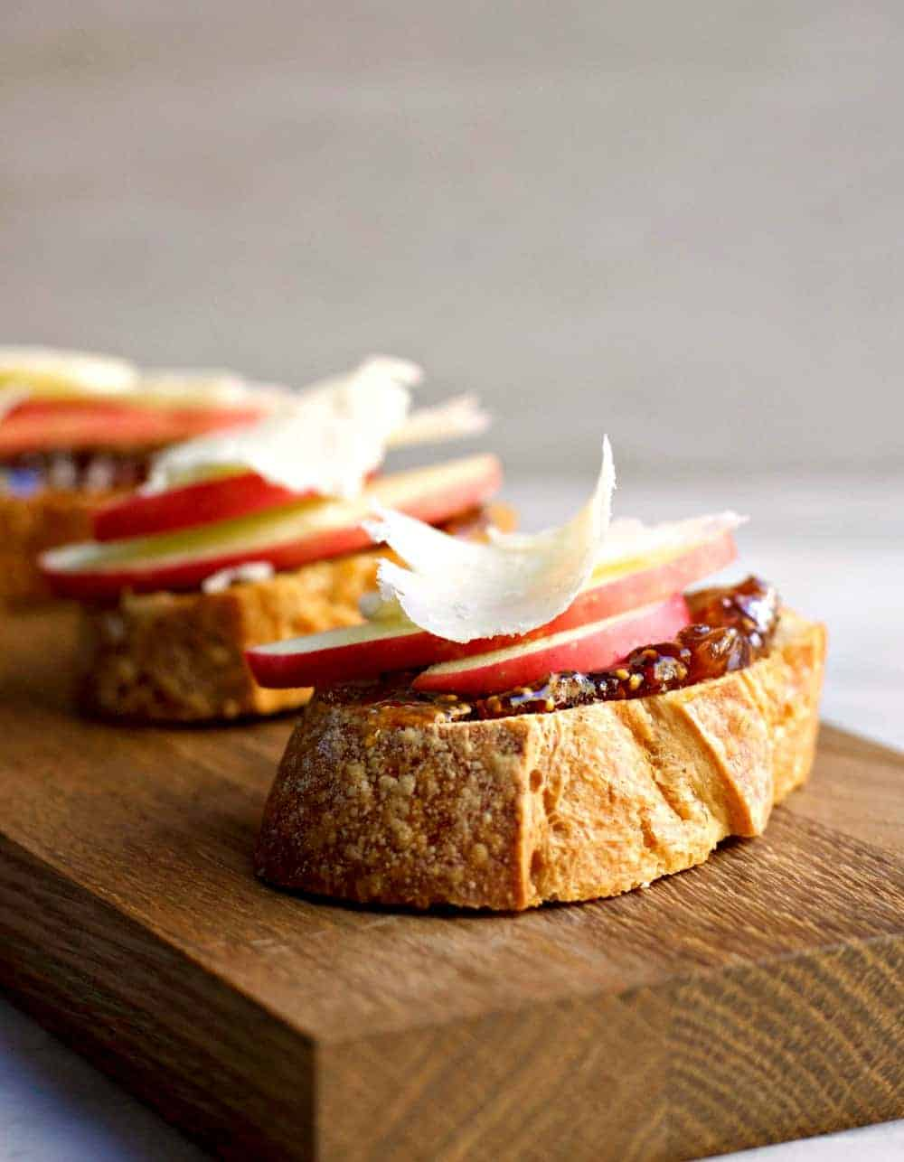 Apple Crostini with Fig Jam and Pecorino served on a wooden board