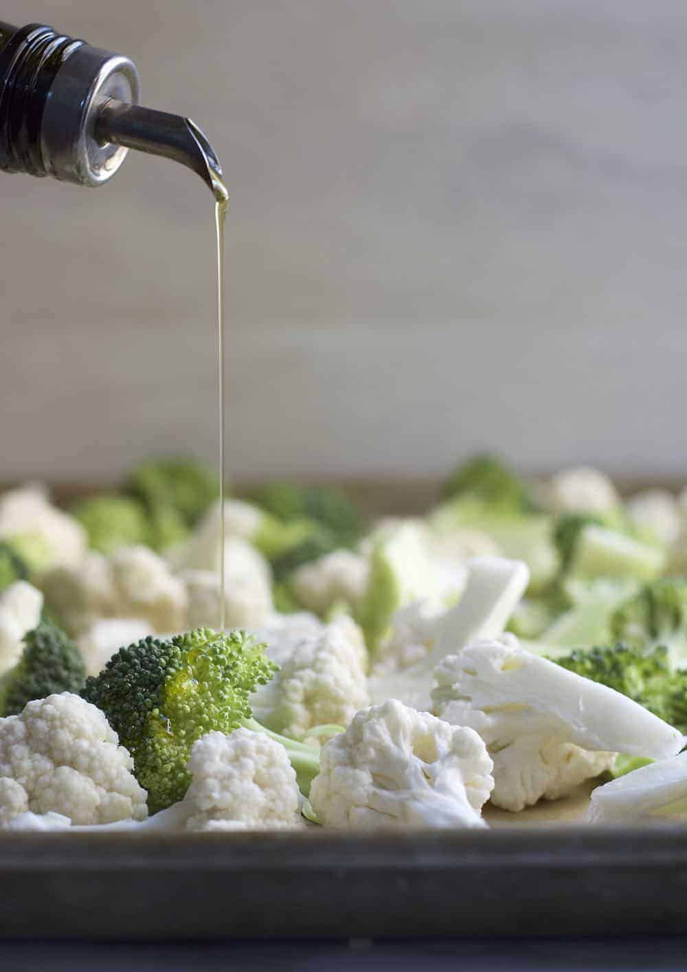 Drizzling Olive Oil on raw Broccoli and Cauliflower