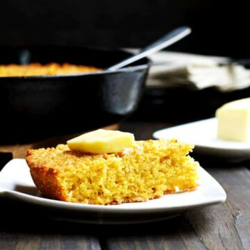 Skillet-Cornbread-served-with-butter on a white plate