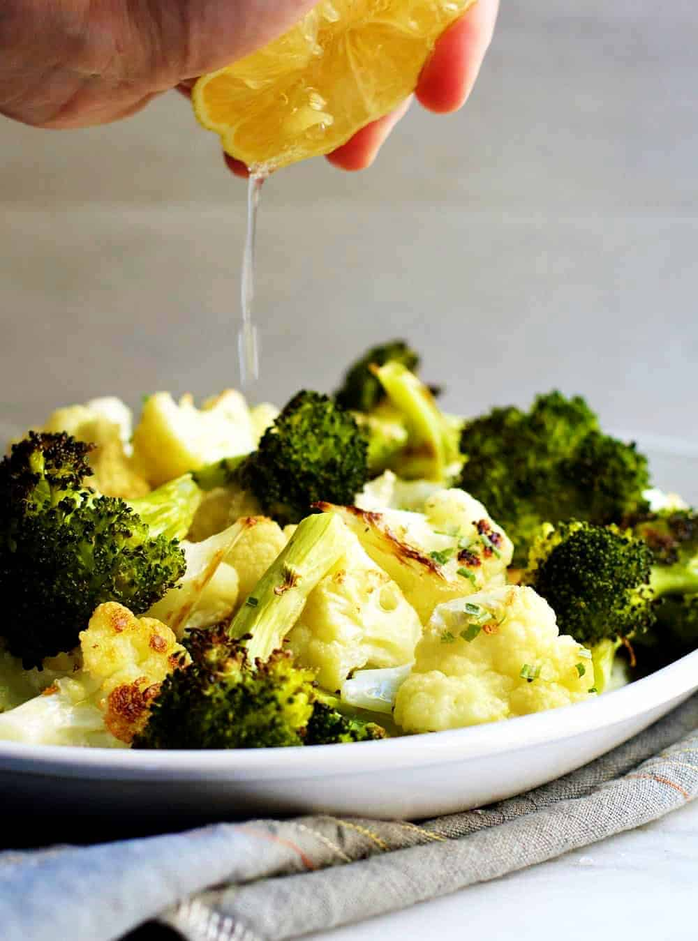 Squeezing Fresh Lemon over Roasted-Broccoli-and-Califlower
