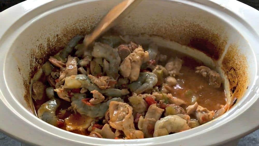 Stirring in Shrimp to finish Cooking in Slow Cooker Jambalaya
