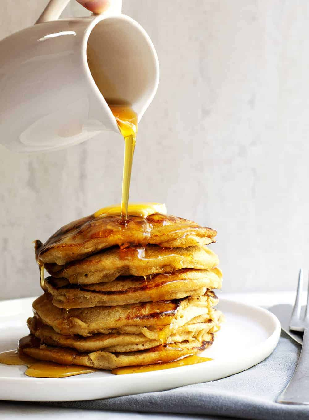 Pouring Syrup over Banana Oatmeal Pancakes