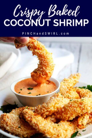 crispy baked coconut shrimp served on a white plate being dipped into remoulade sauce