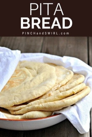 Fresh homemade pita bread wrapped in a kitchen towel and served in a white bowl