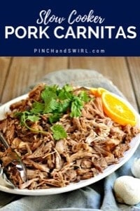 Slow cooker carnitas served on a white oval platter with a fresh orange wedge
