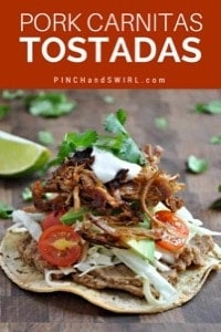 Pork carnitas tostada served on a white plate