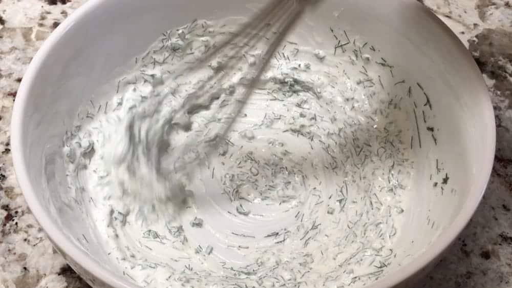 whisking creamy cucumber salad dressing