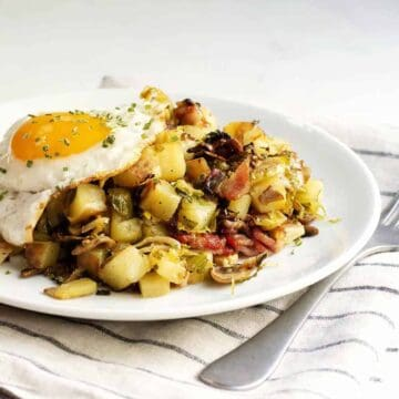 Sweet-Potato-Hash-topped with-fried-egg-on-white-ceramic-plate