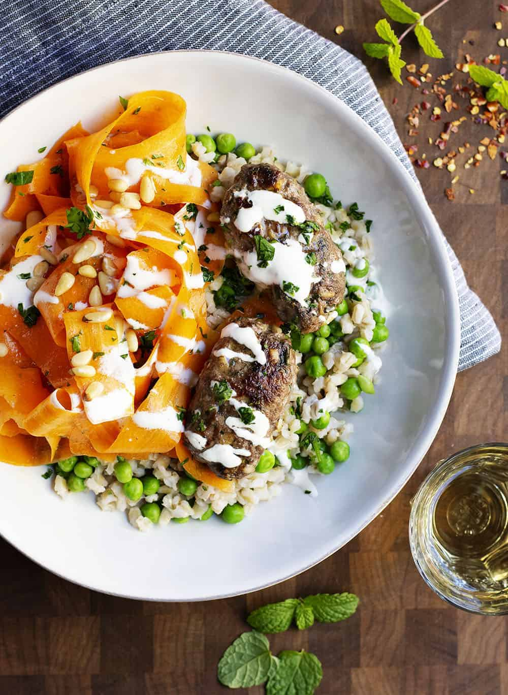 Lamb Kofta served with carrot salad and barley with peas in a white bowl
