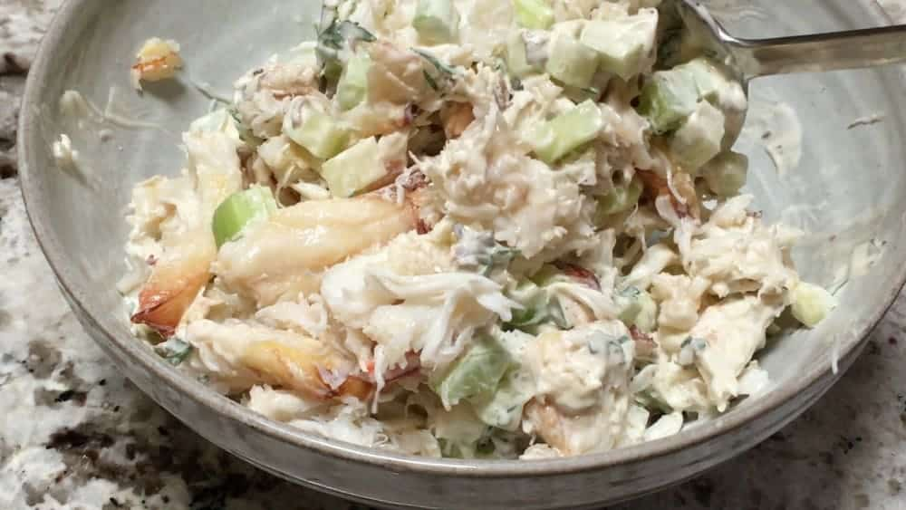 tossing crab salad to coat with dressing