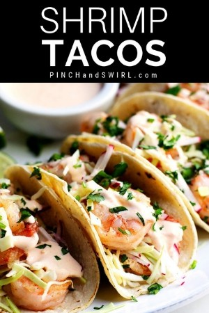 shrimp tacos arranged on a platter with a small bowl of shrimp taco sauce