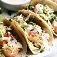 Shrimp Tacos served on a platter with shrimp taco sauce