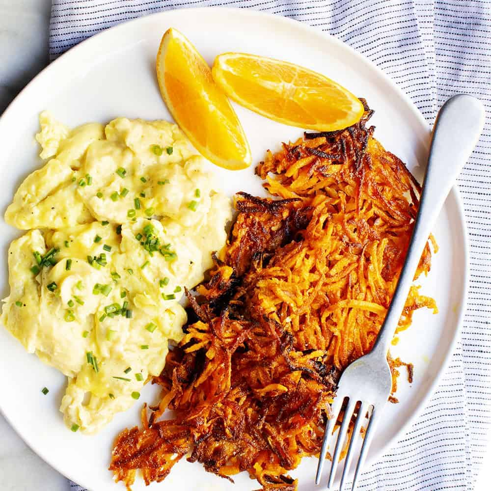 Sweet Potato Hash Browns with scrambled eggs on a white plate