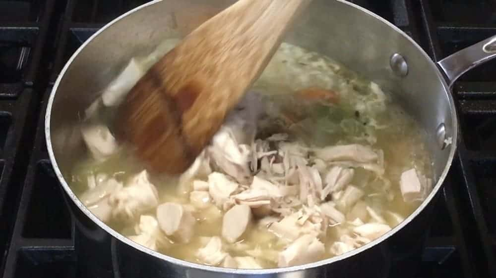 adding chicken to chicken noodle soup