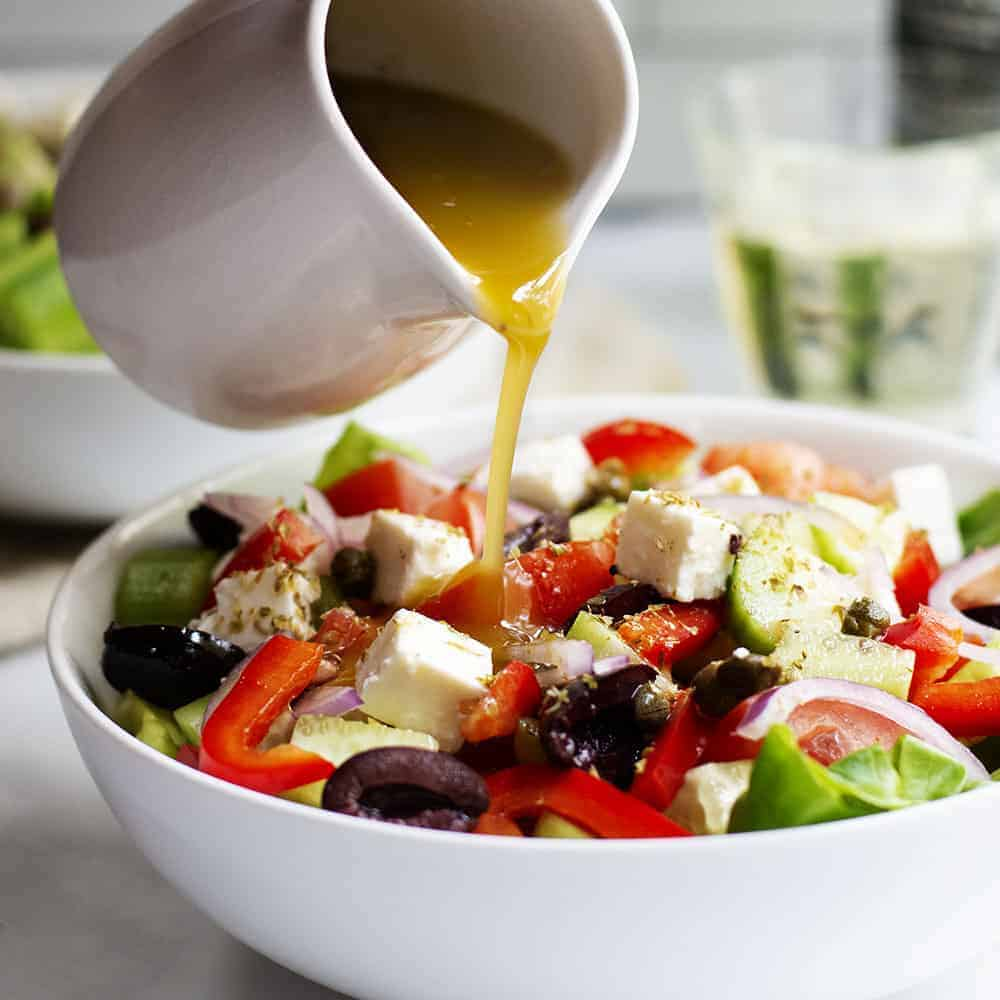 Greek Salad Dressing pouring from a white pitcher