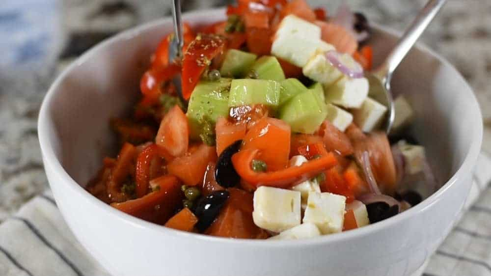 tossing greek salad with dressing
