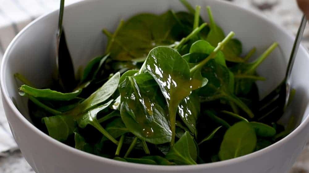 tossing spinach with honey black pepper dressing