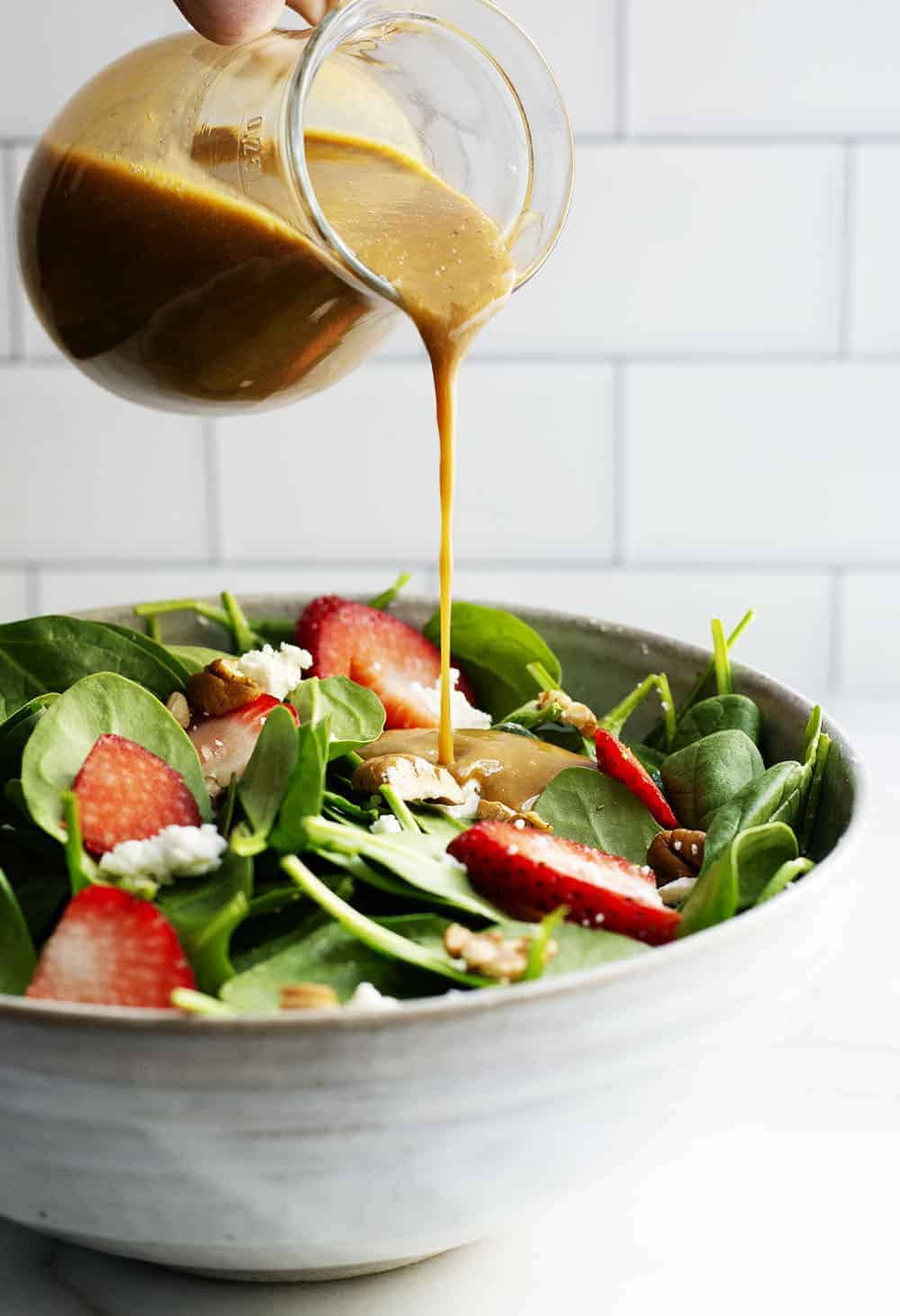 pouring balsamic vinaigrette from glass pitcher